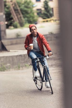 Photo for Young man riding vintage bicycle and coffee to go - Royalty Free Image