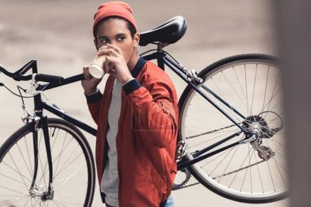 Photo for Man with vintage bicycle drinking coffee to go and looking away - Royalty Free Image