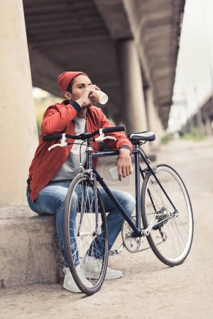 Man with bicycle drinking coffee to go