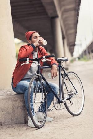 Photo for Young man with vintage bicycle drinking coffee to go - Royalty Free Image