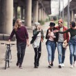 Group of young stylish people walking outdoors...