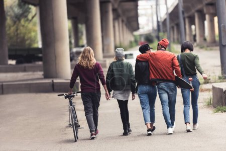 Photo for Back view of young stylish people walking by industrial district - Royalty Free Image