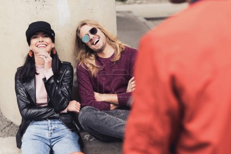Photo for Loughing young couple talking with friend outdoors - Royalty Free Image