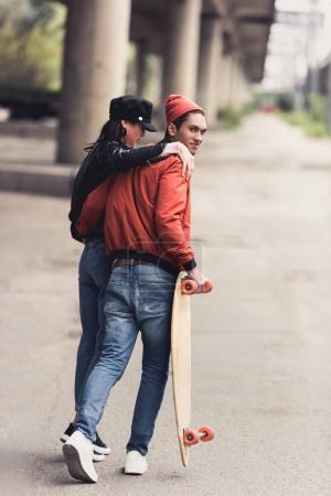 Photo for Young couple with skateboard walking by industrial district - Royalty Free Image