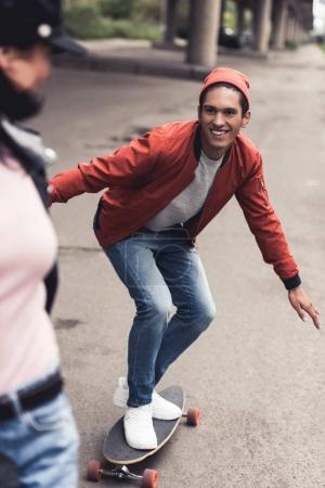 man riding to girlfriend on skateboard