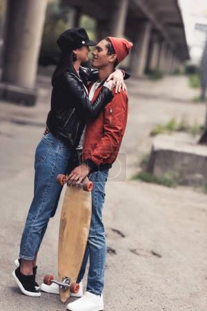 couple with skateboard embracing