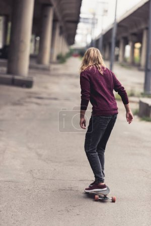 Photo for Back view of handsome young man riding skateboard under bridge - Royalty Free Image