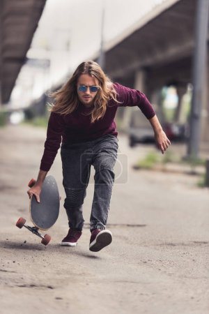Photo for Handsome young man riding skateboard under bridge - Royalty Free Image