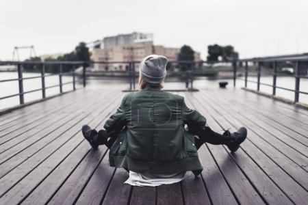 woman sitting on wooden pier