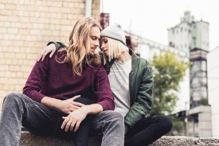 Photo pour Élégant jeune couple assis à l'extérieur et embrasser - image libre de droit