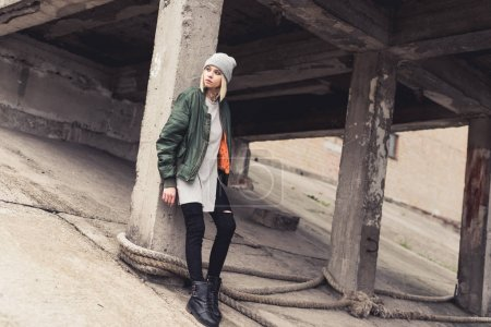 Photo for Thoughtful young woman leaning back on industrial building column - Royalty Free Image