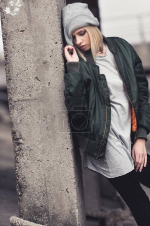 Photo for Beautiful young woman leaning back on industrial building column - Royalty Free Image