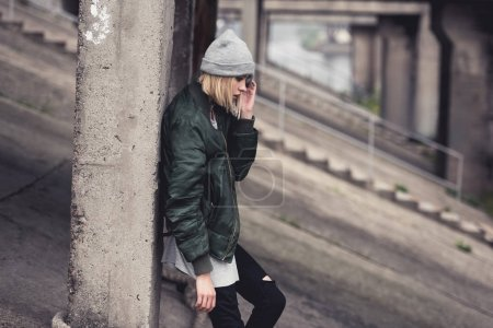 Photo for Stylish young woman leaning back on industrial building column - Royalty Free Image