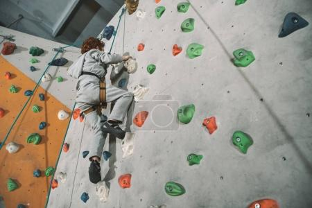 red-headed boy climbing wall