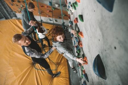 Photo pour Petit garçon dans un harnais escalade un mur au gymnase avec son père lui fixer à l'arrière - image libre de droit