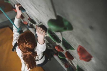 Photo pour Capture d'angle élevé de petite fille rousse un mur avec des poignées au gymnase d'escalade - image libre de droit