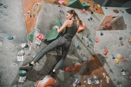 Photo for Full-length shot of young woman in sportive attire climbing a wall with grips at gym - Royalty Free Image