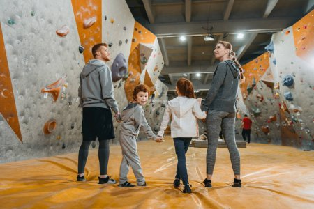 Photo for Full-length shot of family with kids holding hands and standing in a row at gym - Royalty Free Image