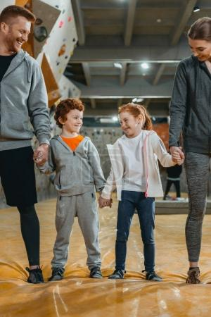 Photo pour Plan complet de la famille heureuse avec les enfants tenant la main et debout dans une rangée à la salle de gym - image libre de droit