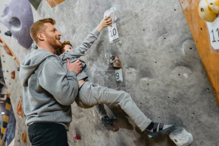 Dad teaching son how to climb