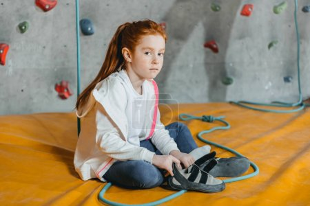 Little girl sitting on mat in gym