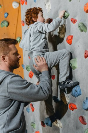 Photo for Little boy in a harness climbing a wall with grips at gym with his father securing him from the ground - Royalty Free Image