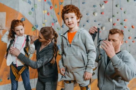 Parent securing children in harnesses