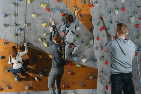 Two little kids climbing wall