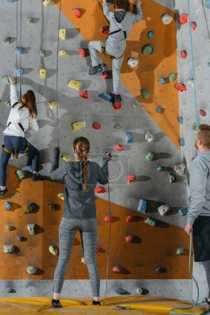 Photo for Full-length shot of two little kids climbing a wall at gym and their mother and father holding securing ropes - Royalty Free Image