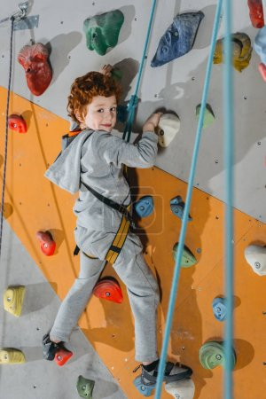 Photo for Full-length shot of little boy in a harness climbing a wall with grips at gym and looking at camera - Royalty Free Image