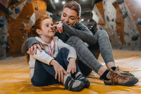 Girl and mom hugging on mat at gym