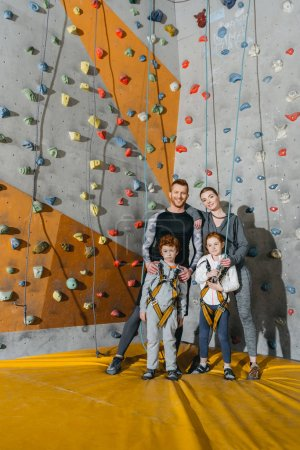 Photo for Family with children standing together near climbing walls at gym and looking at camera - Royalty Free Image