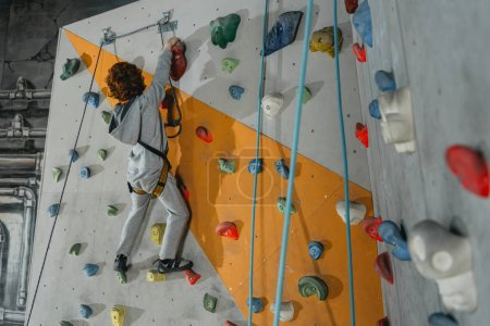 Photo for Full-length shot of little boy in a harness climbing a wall with grips at gym - Royalty Free Image