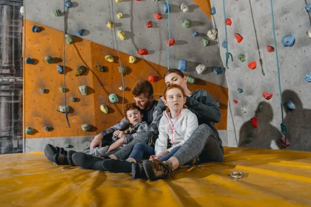 Photo for Family with children sitting on a mat at gym with climbing walls in the background - Royalty Free Image