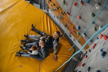 Photo pour Plan grand angle de la famille avec des enfants assis sur un tapis à la salle de gym avec des murs d'escalade en arrière-plan - image libre de droit
