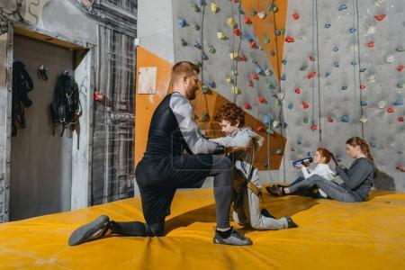 Photo pour Plan complet de papa fixant son petit fils dans un harnais pour mur d'escalade avec poignées à la salle de gym - image libre de droit