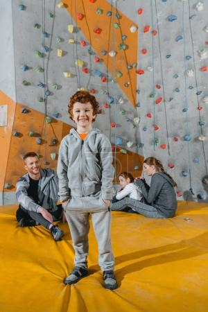 Smiling little boy in front of a climbing wall