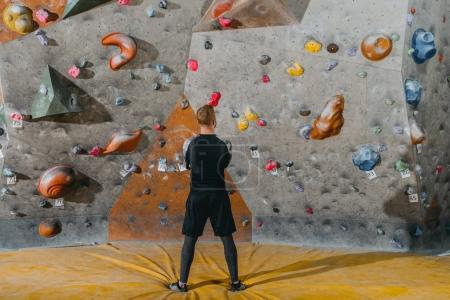 young man in front of climbing wall