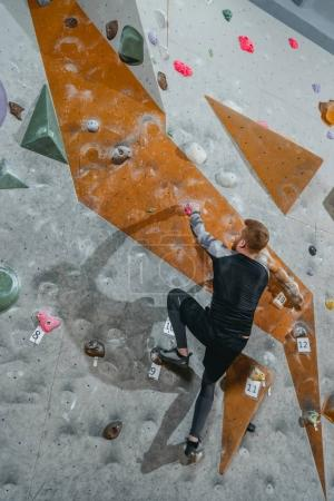 Man climbing wall with grips