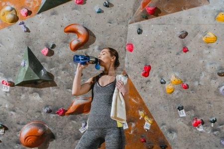 Sportive woman drinking water
