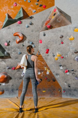 Photo for Full-length shot of a young woman in sportive attire posing in front of climbing wall - Royalty Free Image