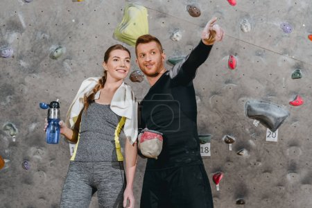 Photo pour Demi-longueur coup de jeune homme en tenue sportive montrant quelque chose à la femme en pointant - image libre de droit