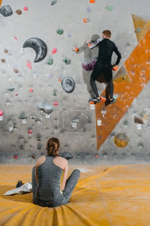 young man climbing wall with grips