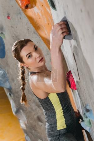 Photo pour Plan à mi-longueur de la jeune femme en tenue sportive escalade un mur avec poignées à la salle de gym - image libre de droit