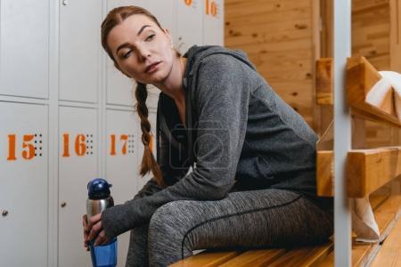 Woman sitting on bench in locker room