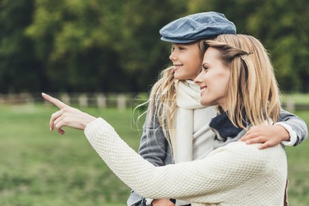 Photo for Stylish mother and daughter in autumn outfit hugging and pointing at countryside - Royalty Free Image