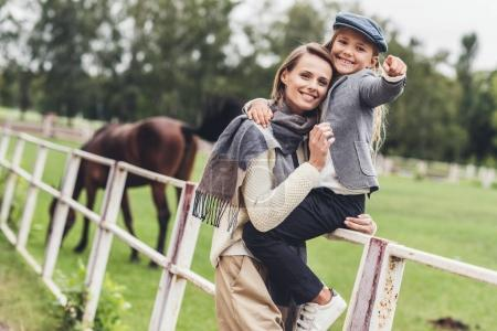 family at paddock with horse