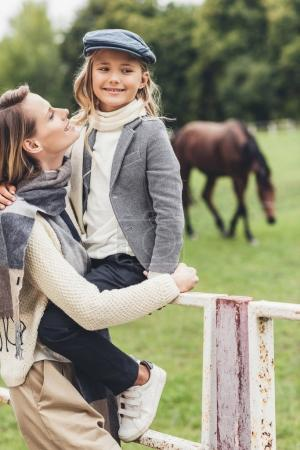 happy family at paddock with horse