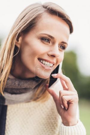 Photo pour Portrait de jolie femme blonde souriante talking sur smartphone - image libre de droit
