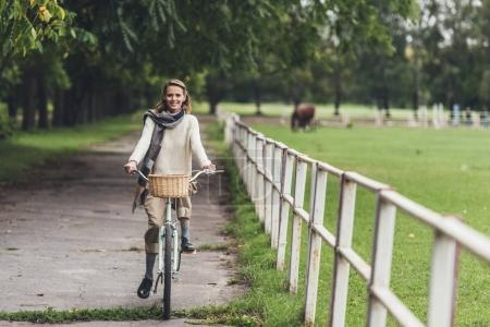 Photo for Attractive smiling stylish woman riding bike at countryside - Royalty Free Image
